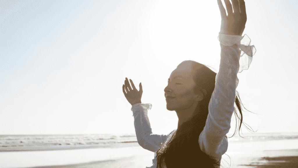 Mulher na beira da praia com os braços levantados para o céu e olhos fechados