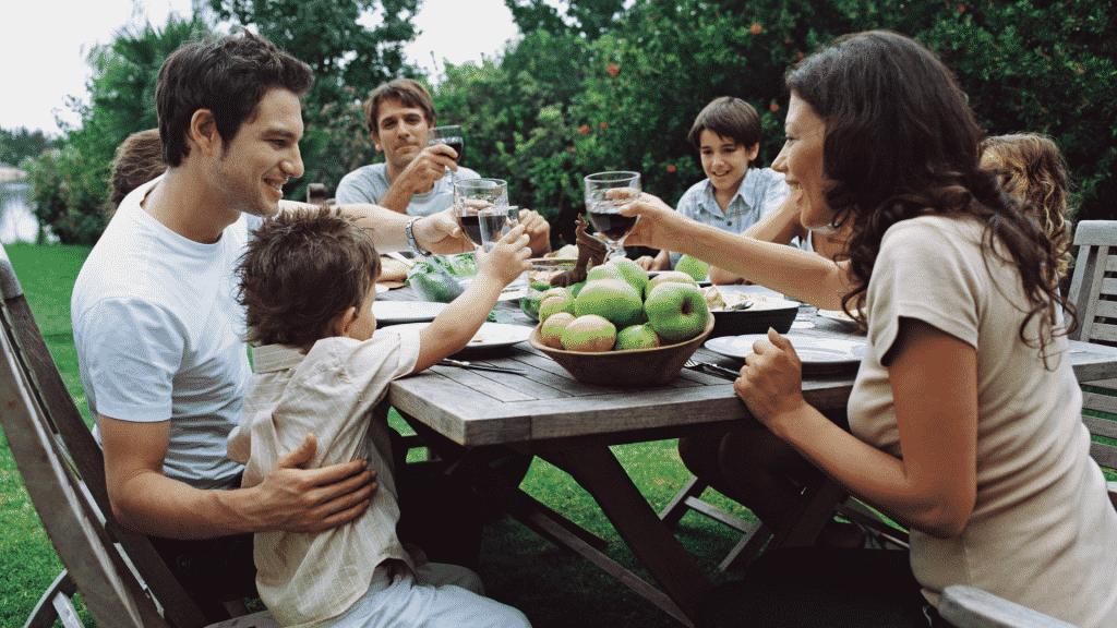 Família e amigos sentados em uma mesa, almoçando