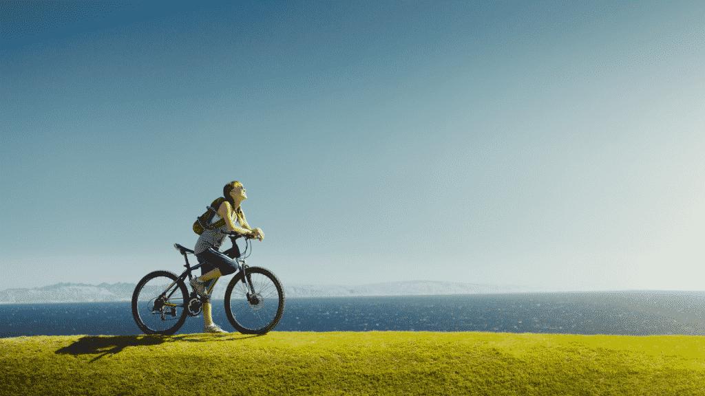 Mulher andando de bicicleta na beira do mar, olhando para o céu azul