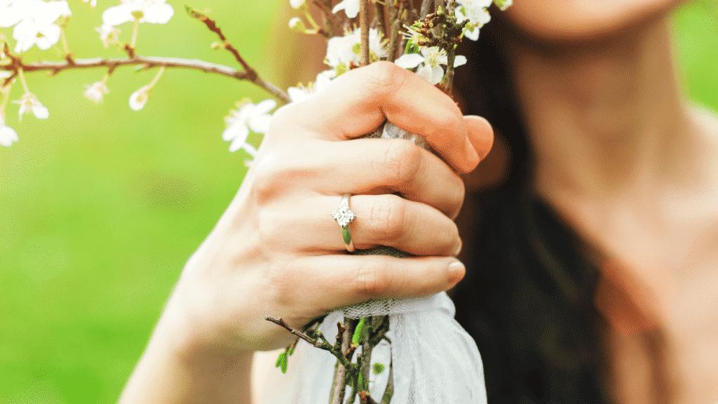 Mulher com aliança no dedo, segurando um ramo de flores
