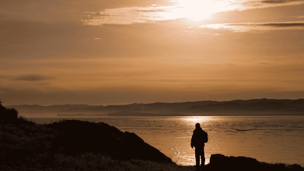 Homem na beira de um rio, olhando para a paisagem
