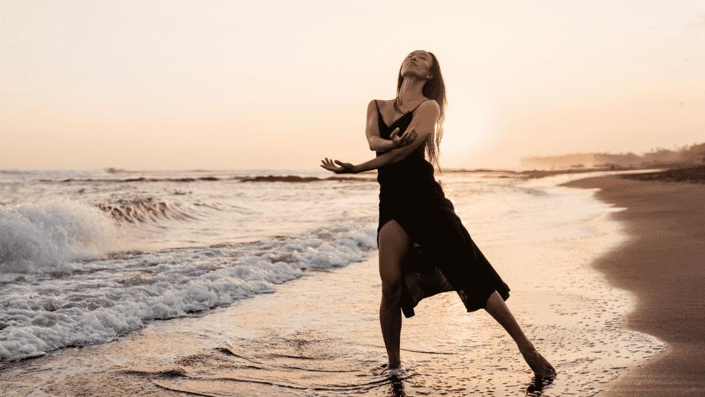 Mulher de vestido dançando descalça na praia