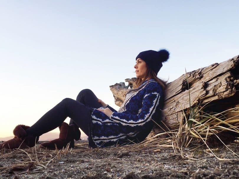 Mulher branca sentada apoiada numa pedra.