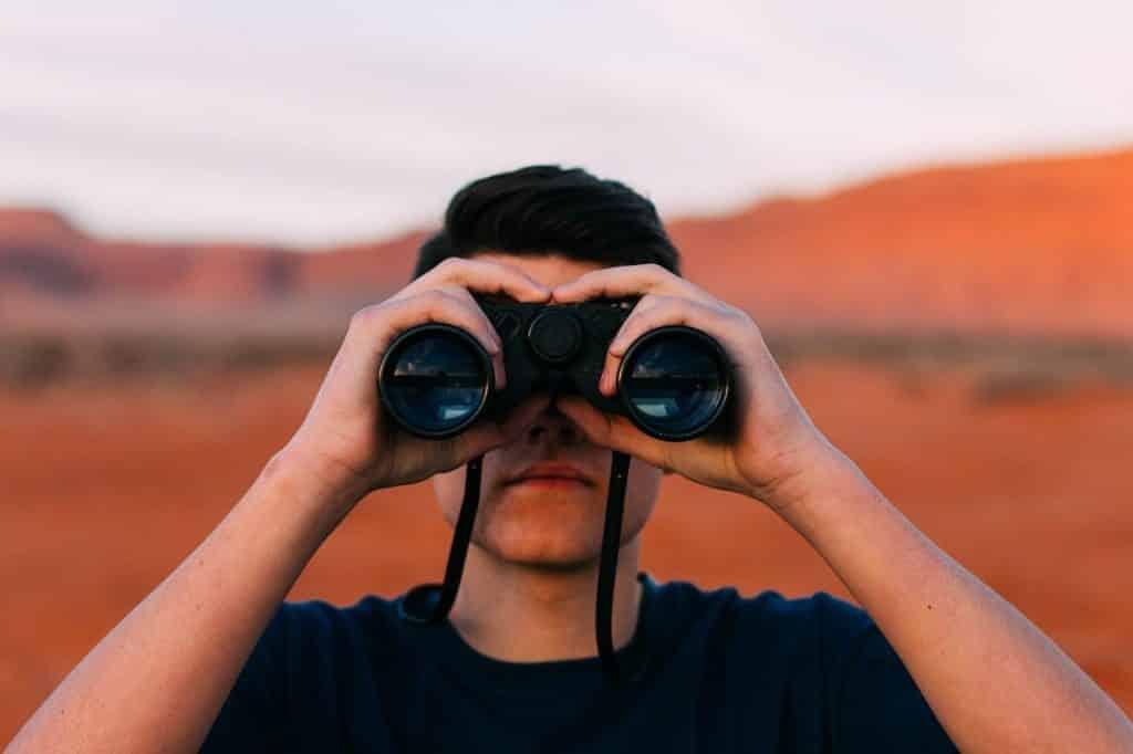 Homem com um binóculo em mãos olhando para frente