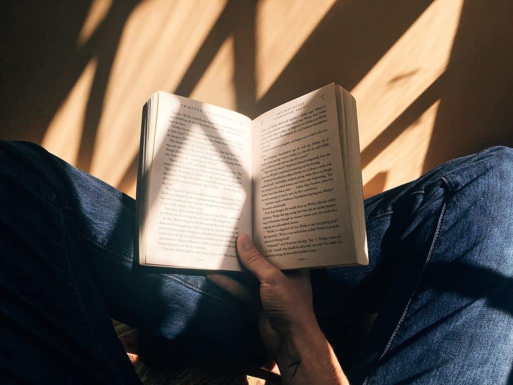 Pessoa branca lendo livro.