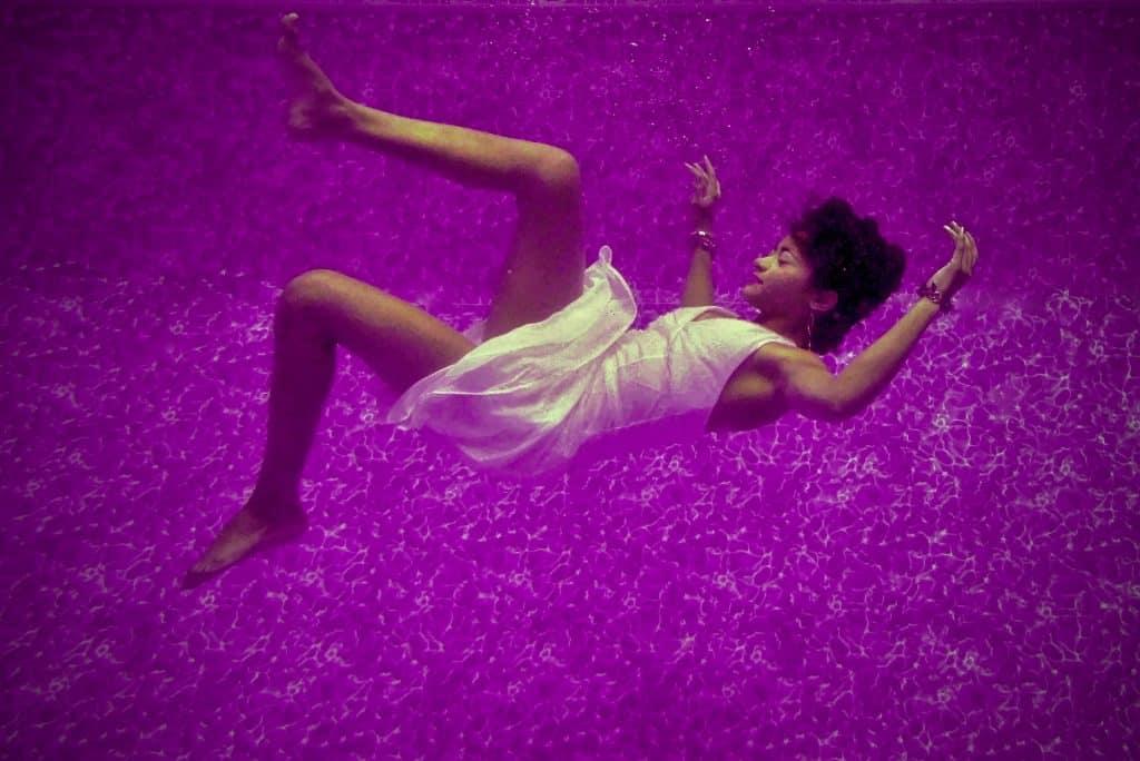 Mulher negra caindo numa piscina roxa.