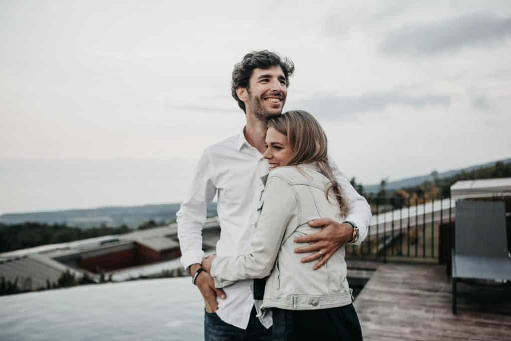 Homem e mulher brancos abraçados sorrindo.