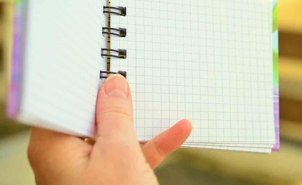 Imagem de uma mão segurando uma agenda