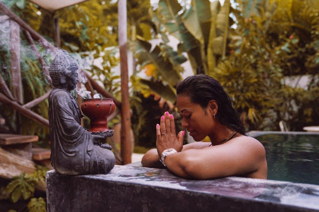 Mulher orando diante da imagem que representa sua religião