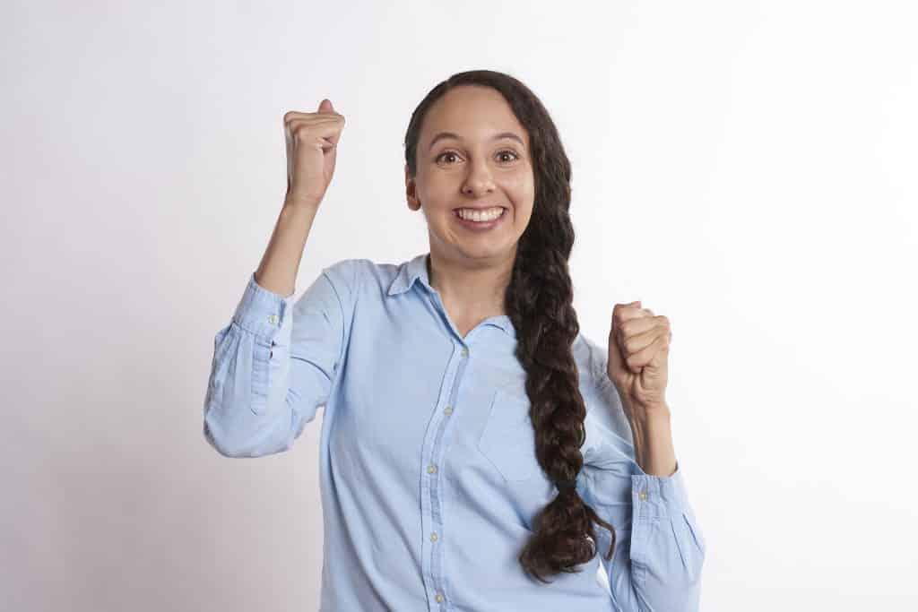 Imagem de uma mulher de cabelos longos e castanhos. Ela usa uma trança. Veste uma camisa azul clara. Ela está confiante, otimista e resiliente.
