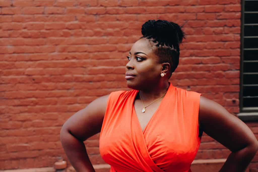 Mulher negra de roupa laranja olhando para o lado.