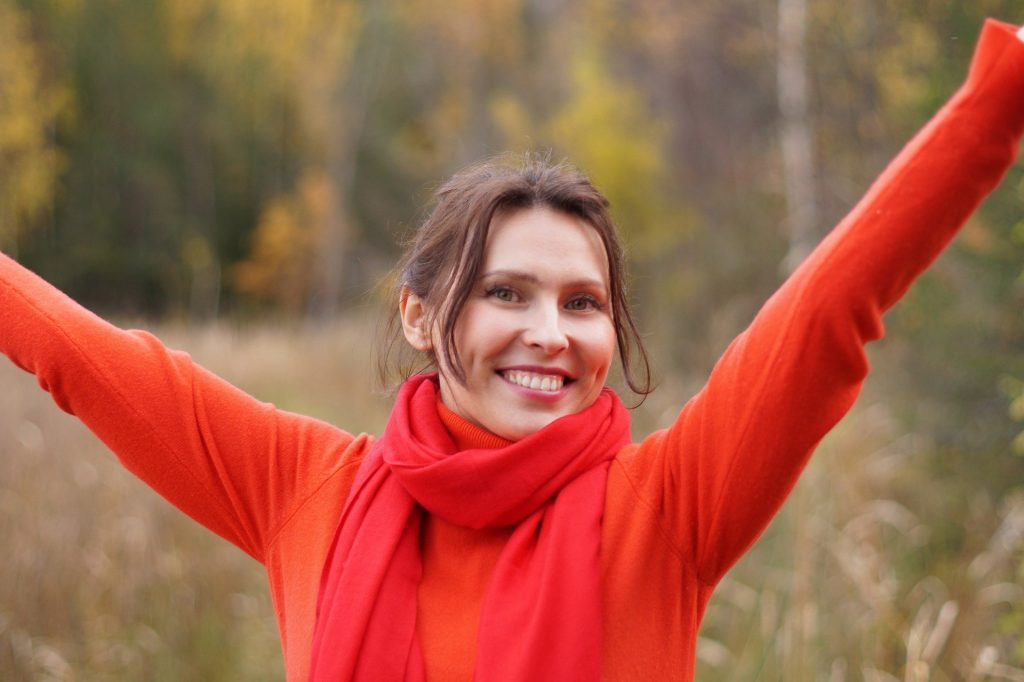 Imagem de uma mulher feliz. Ela está sorrindo e mostrando o quanto ela é resiliente, forte e corajosa mediante os seus problemas. Ela usa uma blusa de manga longa na cor laranja e um cachecol no pescoço na cor vermelha.