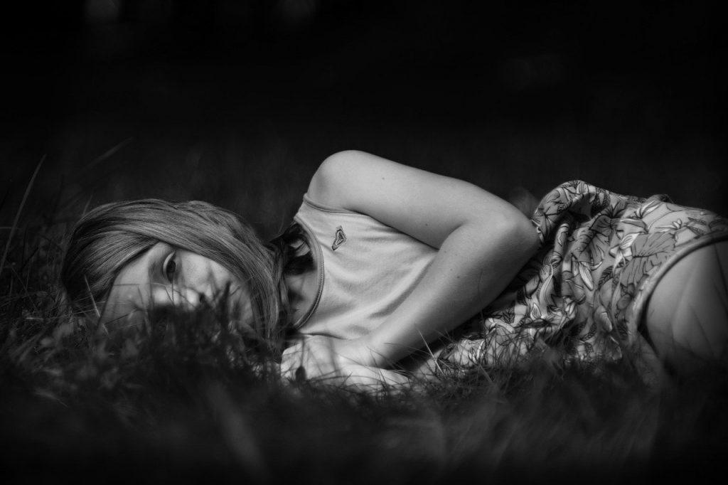 Menina triste deitada em gramado.