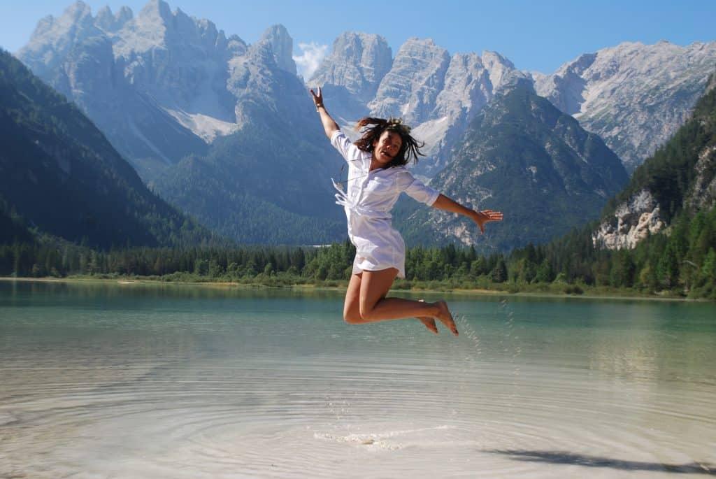 Imagem de uma jovem garota vestindo uma samisa e um shorts na cor branca. Ela está dando um salto em um lago.  Ao fundo algumas montanhas e uma floresta com vários pinheiros.