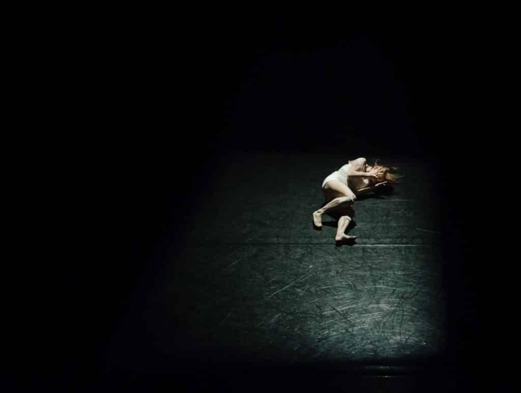 Mulher branca deitada num chão preto.
