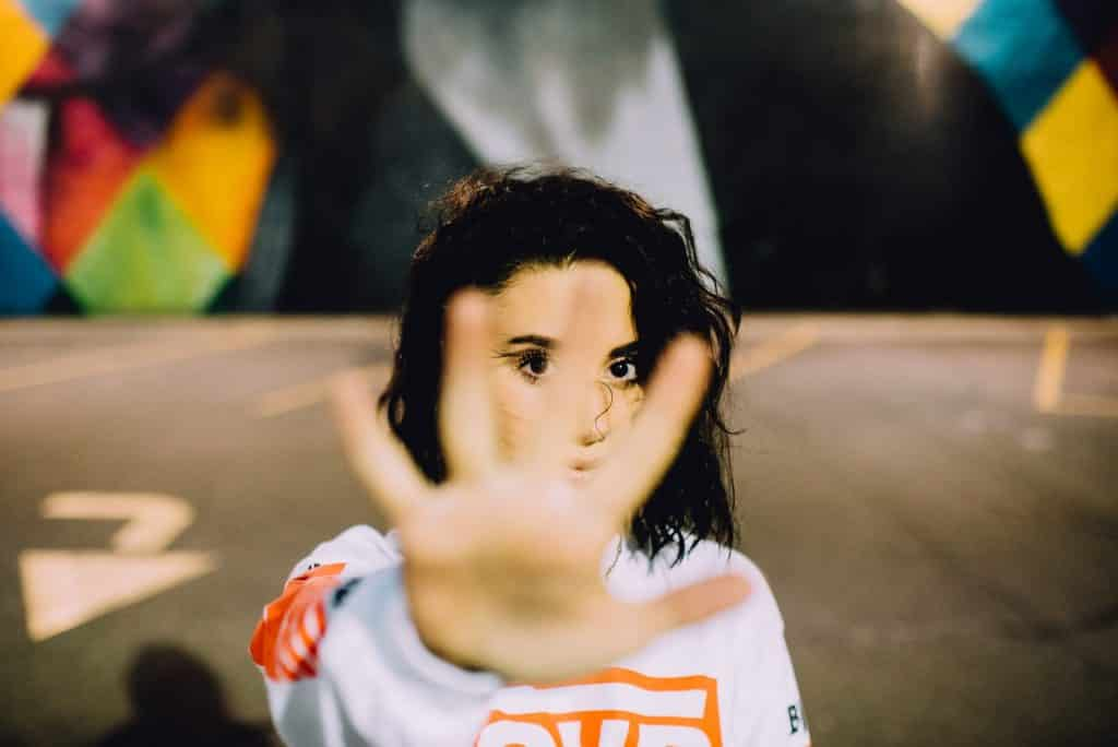 Mulher branca de cabelos curtos e castanhos com a mão aberta em frente ao rosto.