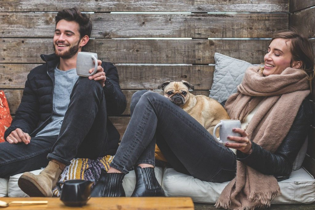 Dois amigos sentados juntos  com um cachorro