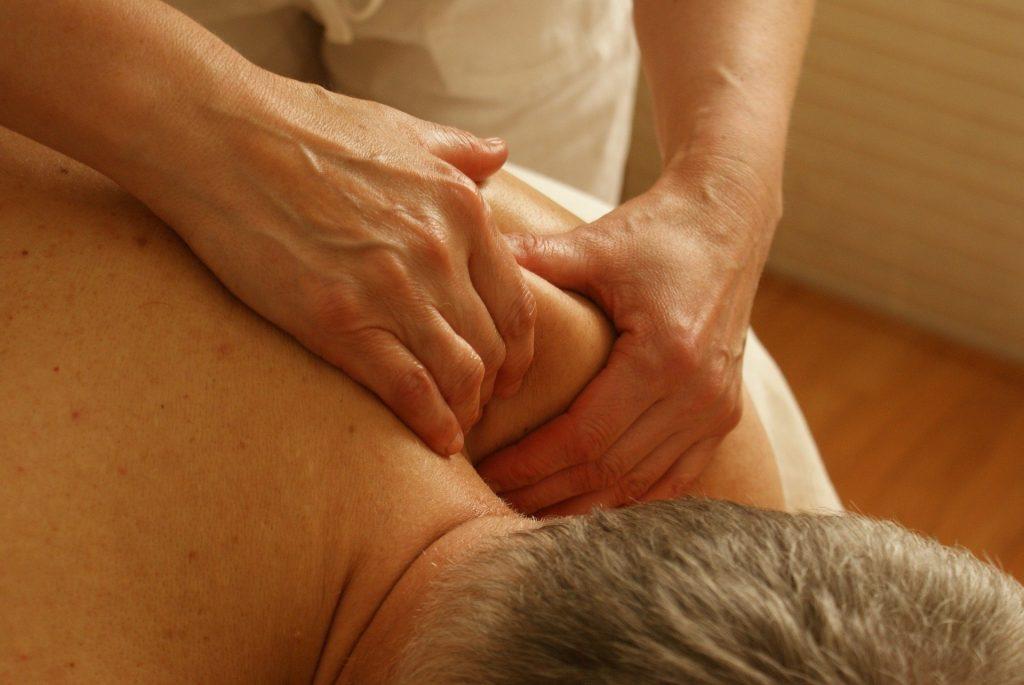 Imagem de um senhor de cabelos grisalhos deitado de costas sobre uma maca. Ele está sem camisa e recebe de  uma terapeuta uma sessão de quiropraxia em seu ombro.