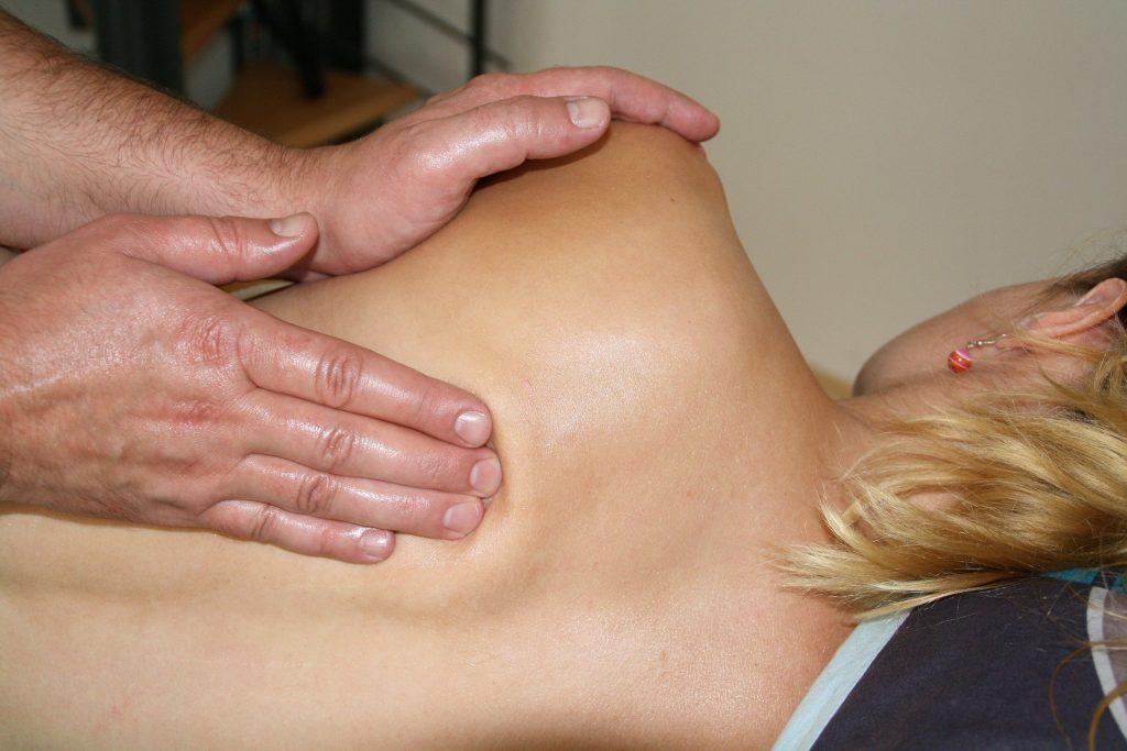 Imagem de uma mulher de cabelos loiros, deitada de lado sobre uma maca. Ela está recebendo uma massagem de quiropraxia nas costas.