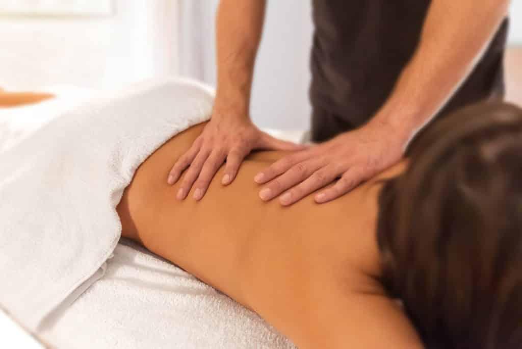 Imagem de uma mulher de cabelos castanhos deitada de bruço sobre uma maca forrada com uma toalha felpuda na cor branca. Ela está recebendo uma massagem de quiropraxia das mãos de um terapeuta.