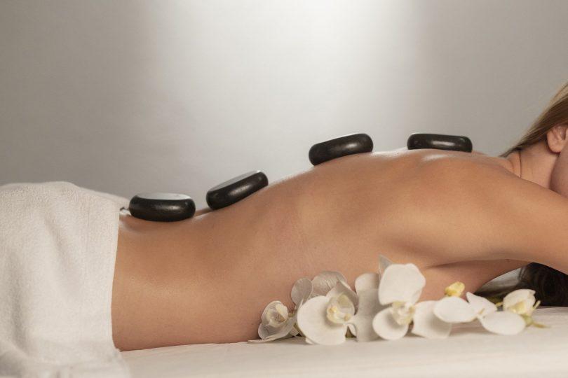 Imagem de uma mulher deitada de bruço em uma maca. Ela está sem blusa e com uma toalha branca sobre as suas nádegas. Ela está com umas pedras sobre as suas costas, recebendo um tratamento de quiropraxia. Ao lado do corpo dela, alguns ramos de flores amarelas completam a imagem.