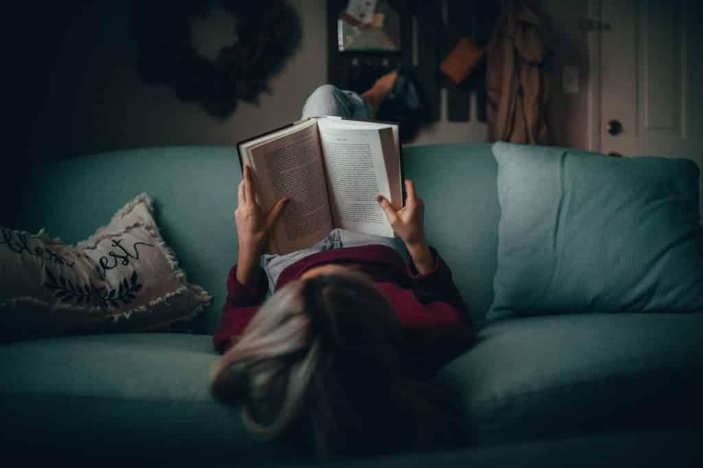 Mulher deitada de cabeça para baixo num sofá enquanto lê livro.