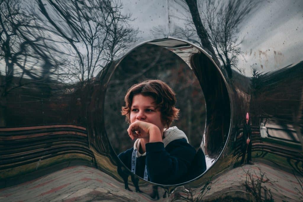 Mulher branca sendo refletida num espelho.