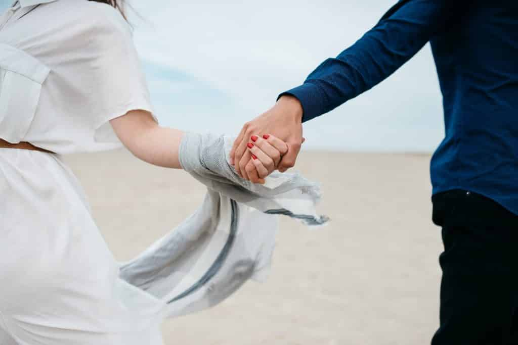 Homem e mulher brancos de mãos dadas.