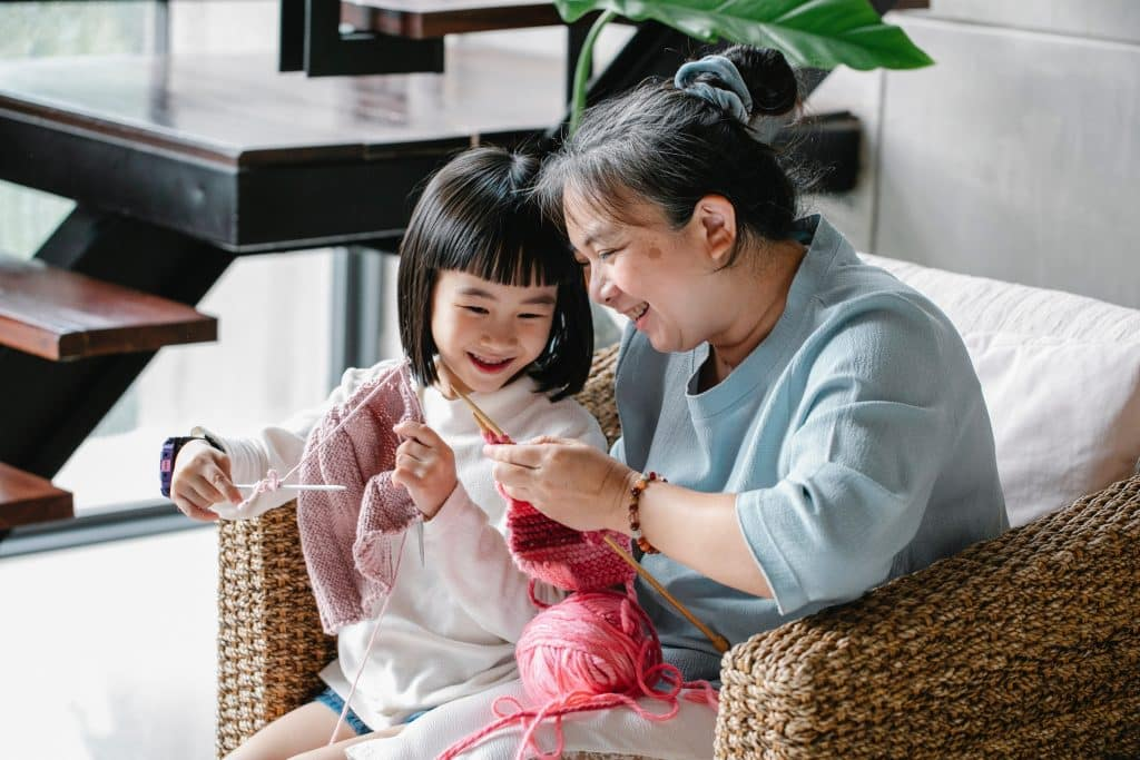 Mãe e filha juntas fazendo tricô