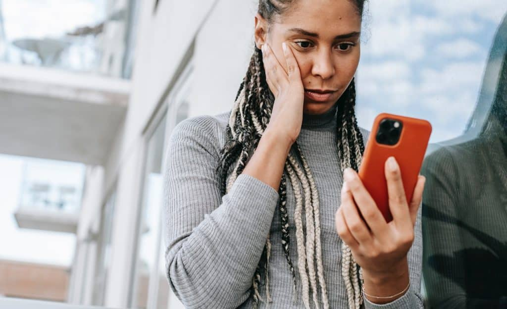 Mulher com a mão apoiada em uma das bochechas. Ela olha para o celular e tem um semblante aflito.