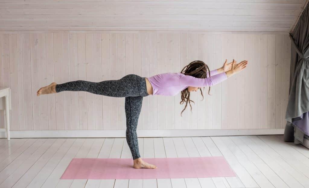 Mulher praticando Yoga em ambiente fechado.