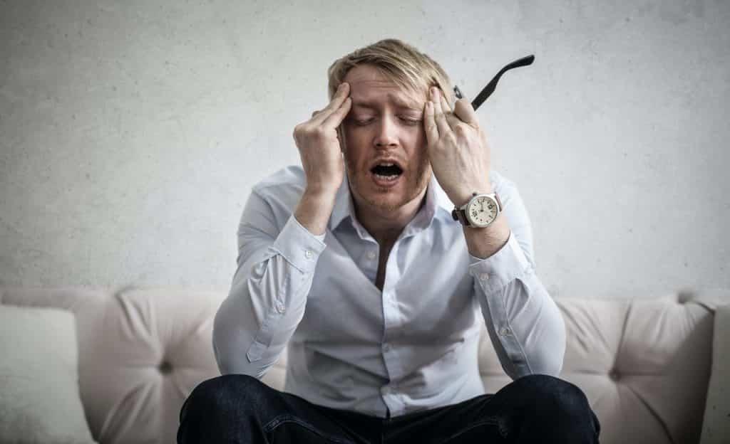 Homem sentado em sofá pressiona as têmporas enquanto segura óculos em uma das mãos. Seu semblante representa o sentimento de dor.