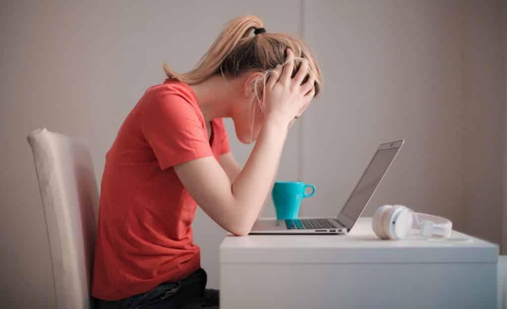 Mulher sentada à mesa, com as mãos na cabeça, apoia os cotovelos na superfície em sua frente; nela, há uma caneca azul, fones de ouvido e um notebook.