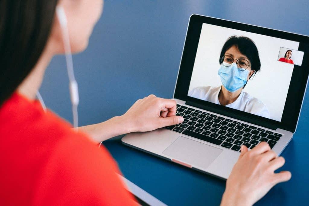 Duas mulheres se falando por vídeo chamada através de um notebook