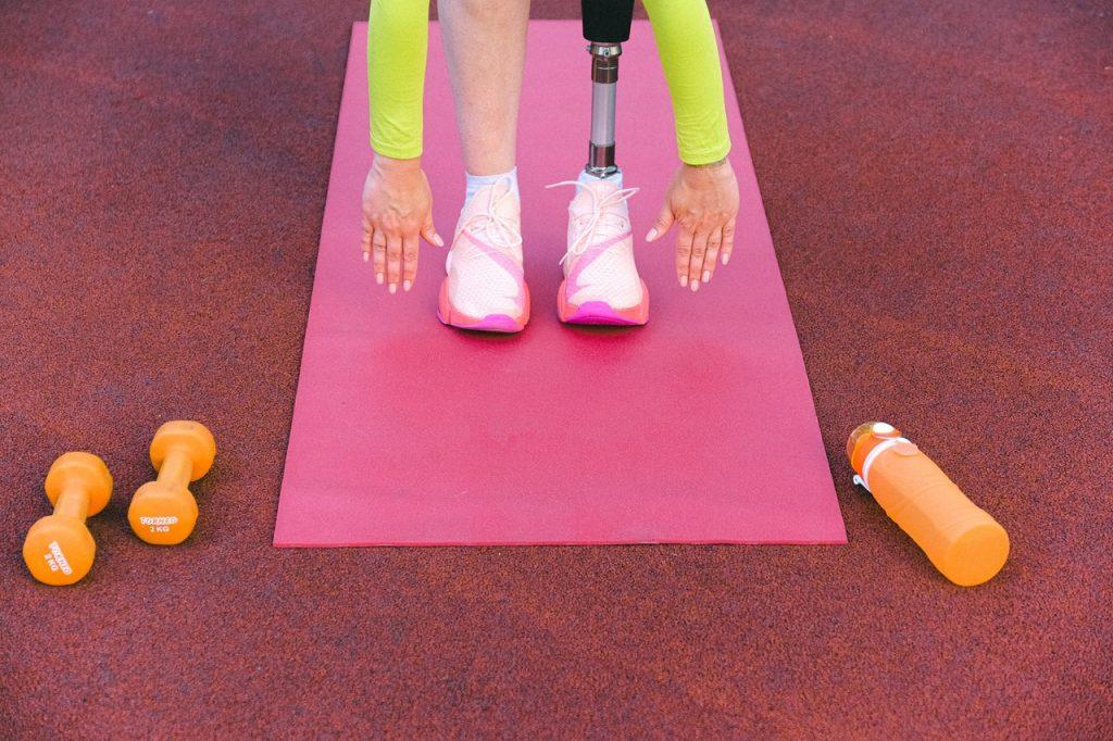 Mulher com perna protética pratica exercícios. Ao lado, há pesos e uma garrafa d'água.