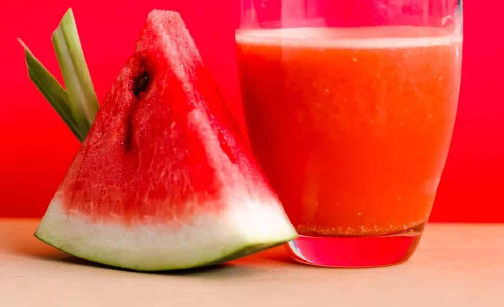 Fatia de melancia ao lado de um copo com o suco da fruta. Ambos estão sobre uma superfície lisa. O cenário é vermelho.