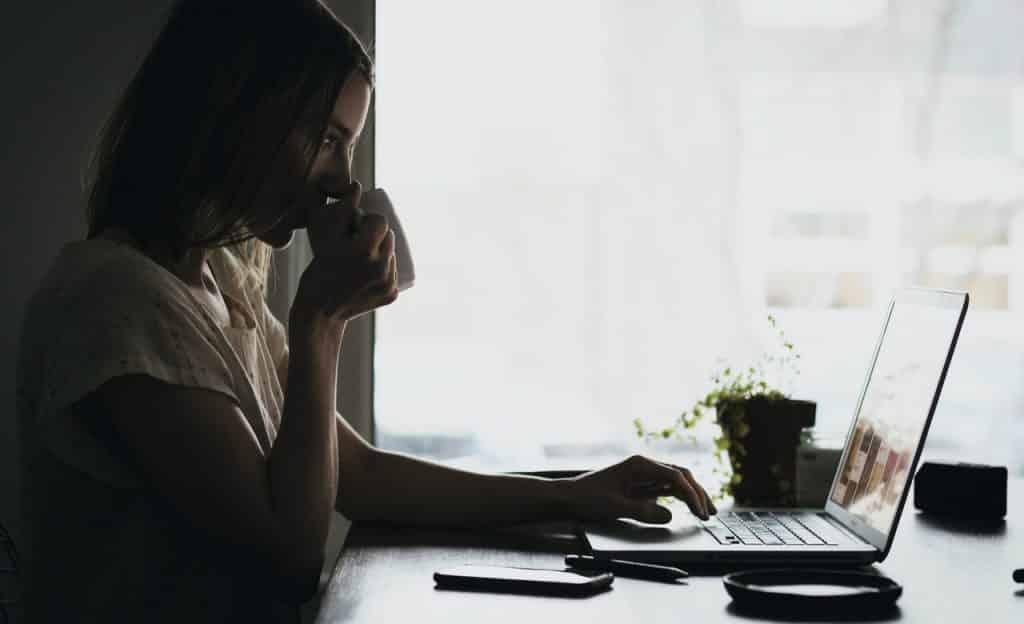 Mulher sentada à mesa mexe em computador. Ela bebe em caneca de porcelana branca.