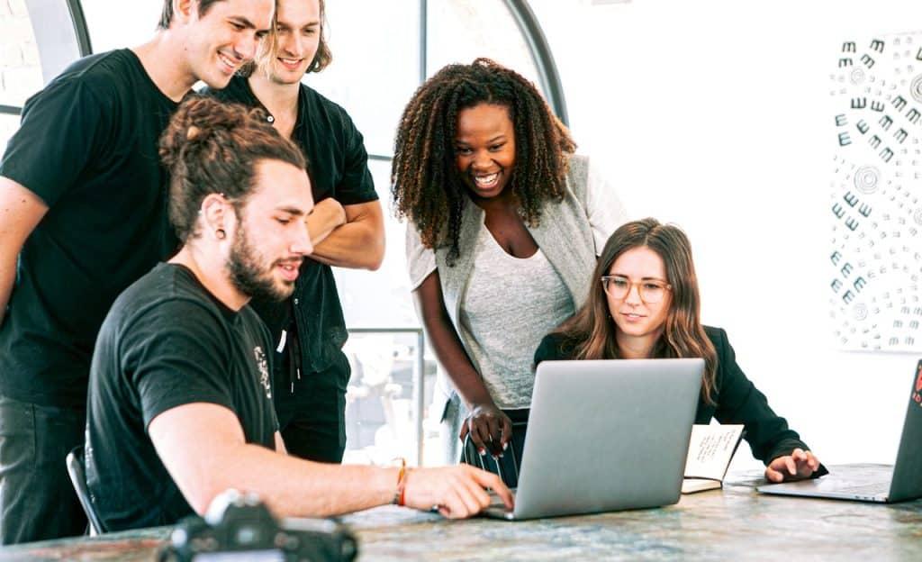 Grupo de cinco pessoas olham computador que está sobre uma mesa. Duas delas, um homem e uma mulher, estão sentados à mesa.