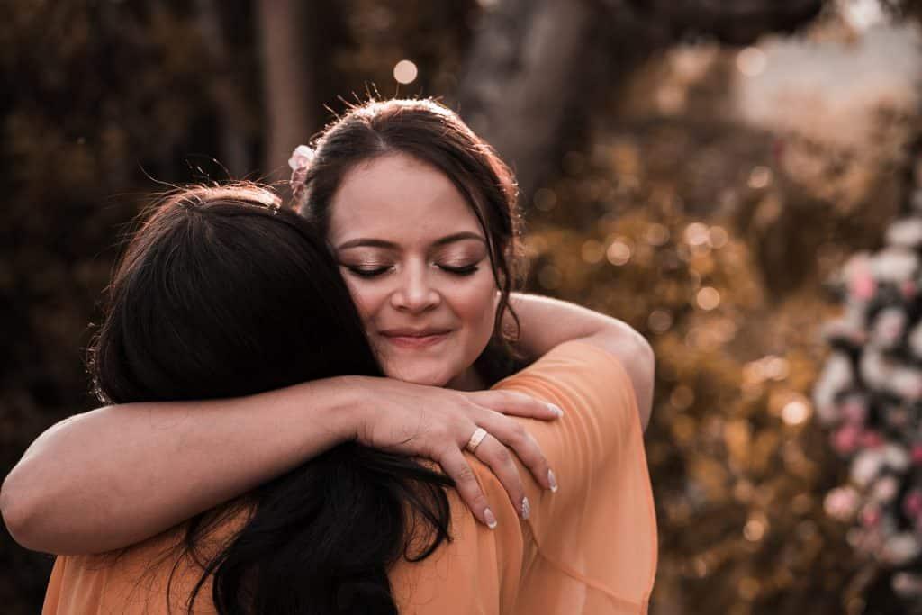Duas mulheres se abraçando. Uma delas usa uma grande aliança de ouro em seu dedo.