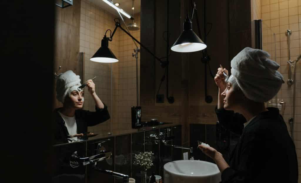 Mulher se olha em espelho e passa produto branco no rosto.