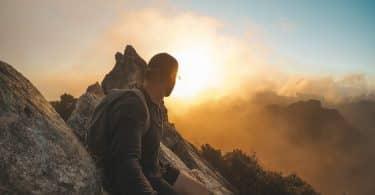 Homem de mochila numa montanha.