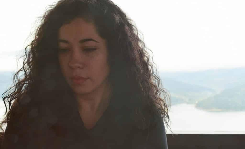 Mulher cabisbaixa com o semblante triste.