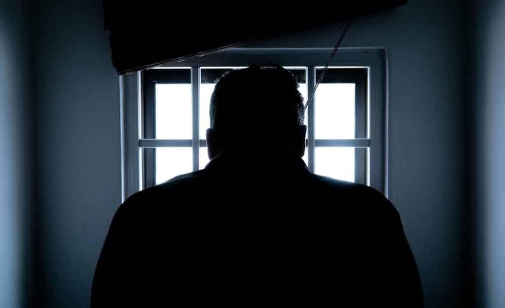 Homem cabisbaixo de costas. Ao fundo, há uma janela. O ambiente é escuro.