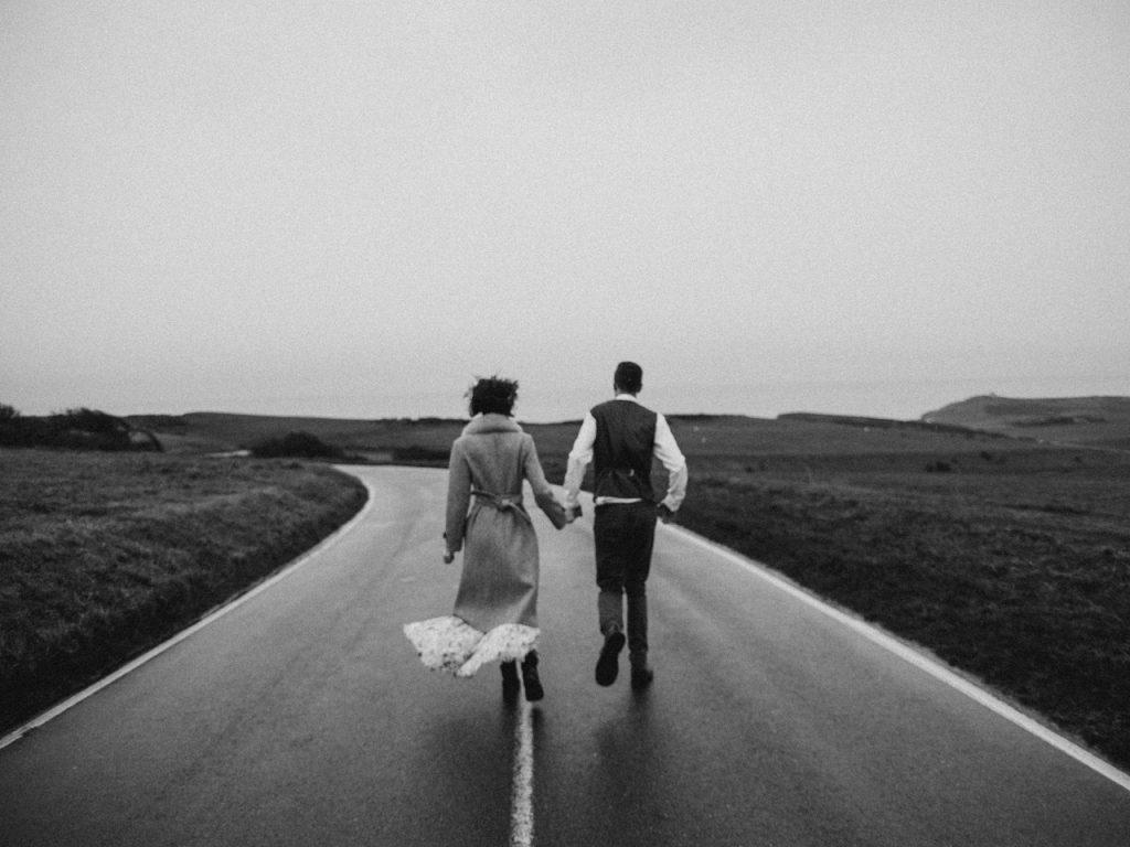 Mulher e homem negros andando numa estrada.
