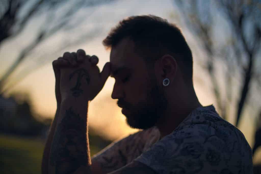Homem com as mãos unidas em frente ao rosto demonstrando fé