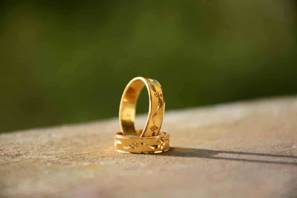 Duas alianças douradas de casamento colocadas uma em cima da outra.