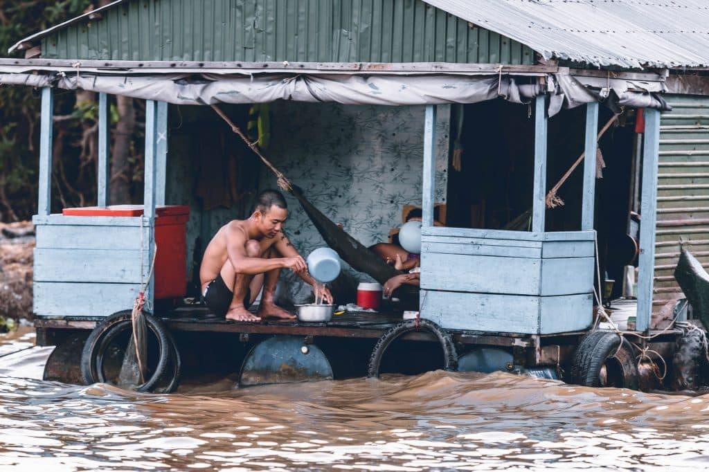 Homem em uma varanda de casa flutuante colocando água em uma vasilha. Abaixo dele está um rio.