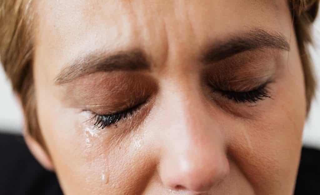 Mulher de olhos fechados chora.