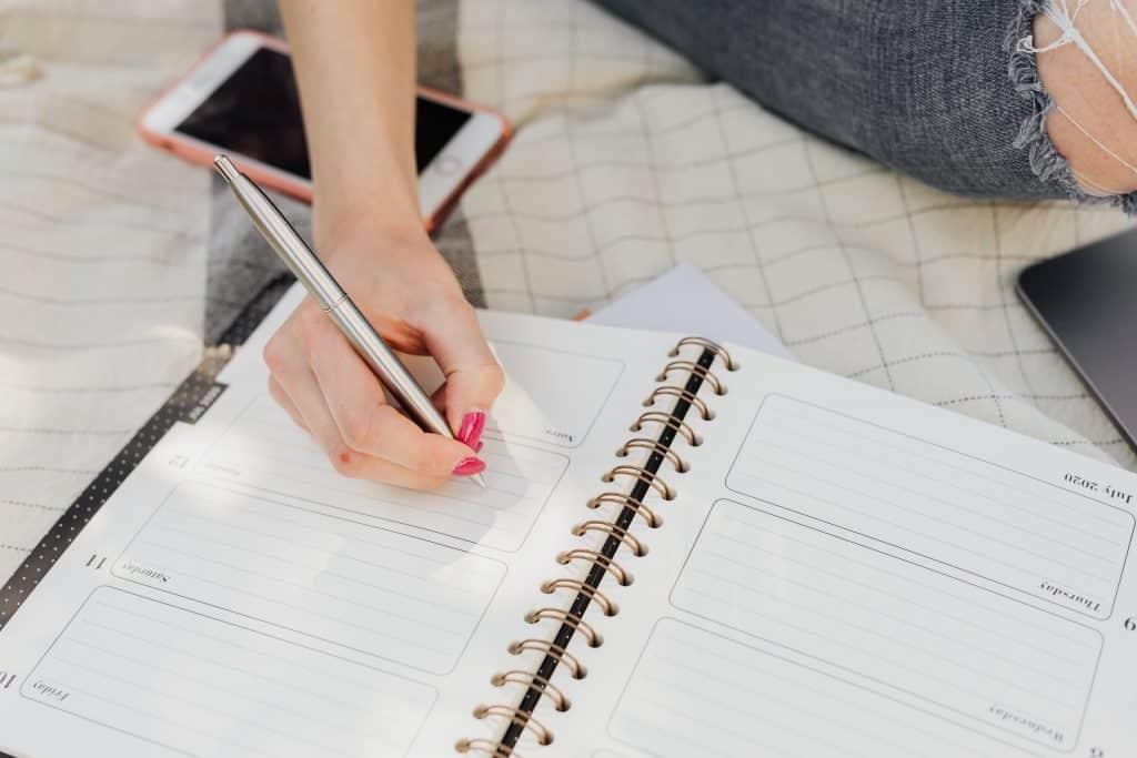 Mulher escrevendo em uma agenda