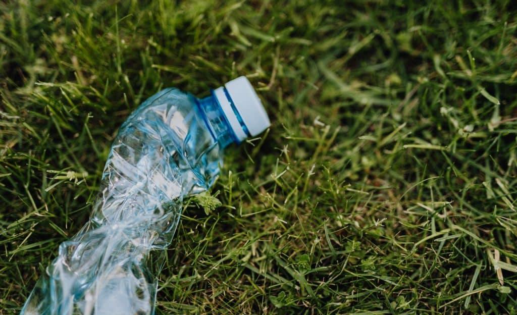 Garrafa plástica amassada sobre gramado.